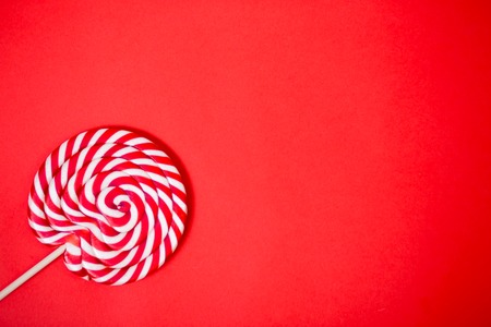 Sweet round red and white lollipop. Colorful striped lollipop on coral background with copy space. Top view. Valentine's day, children's holiday, sweets, candy concept.