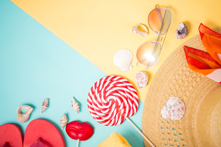 Beach accessories on mint yellow background with copy space. Top view of beige straw sun hat, towel, sunglasses, pink flip flops, headscarf, seashells, lollipops. Summer holiday poster.