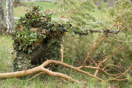Camouflaged sniper in the forest in ambush. Military man aiming a gun, a rifle at the enemy in nature