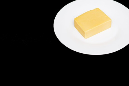 Closeup of a piece of cheese on a white plate on a black background with copy space. Natural dairy products, delicious food concept
