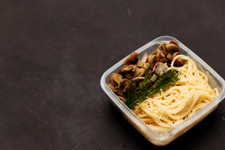 Closeup of pasta with mushrooms in a container on a black background with copy space. Healthy diet, good nutrition concepts.
