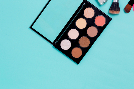 Horizontal blue paper background for text with makeup. Multi colored palette of shadows and face corrector