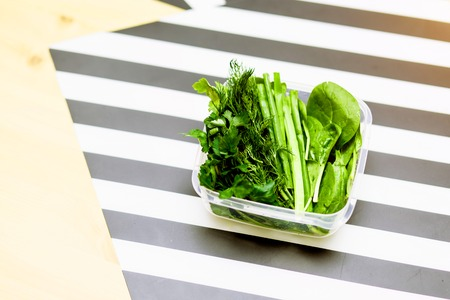 The food in the containers, a healthy diet, good nutrition concepts. Parsley leaves, spinach, dill and onions on the kitchen table with copy space