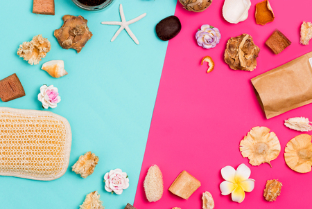 Spa frame of cosmetic products, washcloths, flowers, seashells, scrub on colorful pink and blue background with copy space for text, top view. Flat lay