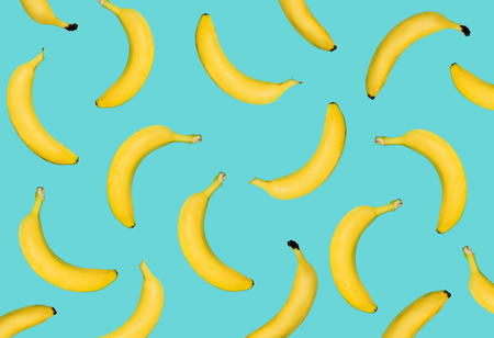 Banane jaune exceptionnelle sur fond bleu pastel. Les fruits tombent de haut en bas