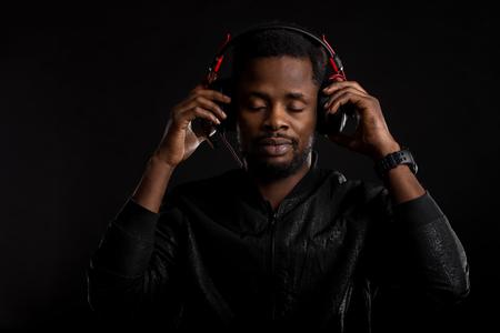 Pleased relaxed bearded dark skinned man listening music in modern black headphones, enjoying with closed eyes on dark background. Closeup og professional african american DJ in earphones.