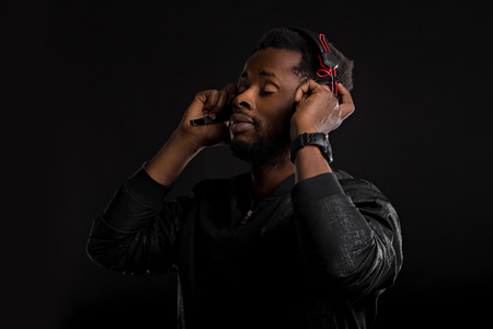 Portrait of dark skinned male with beard listening attentively audiobook or song on headphones, wearing black jacket looking pensively down, standing with crossed hands isolated black background.