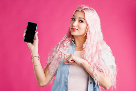 Indoor shot of smiling cheerful pink haired woman pointing with forefinger at screen of smartphone, advertising gadget, dressed in tee shirt, denim shirt, posing on bright background.