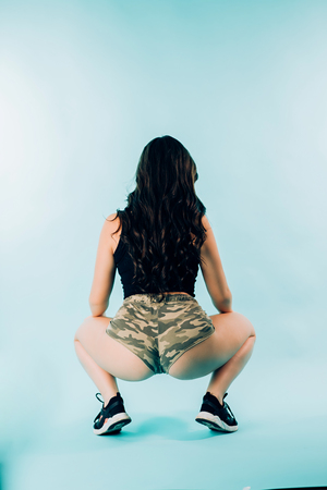Sexy brunette woman dancing twerk on blue background, from behind. A young girl wears camo shorts and a black top, and sat down