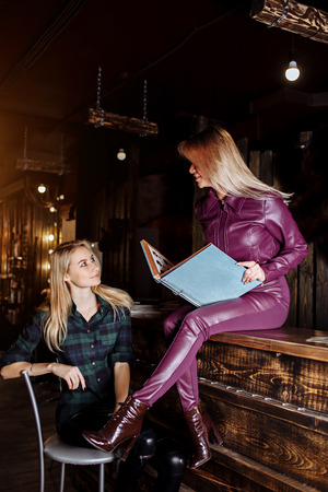 Sensual lovely blonde administrator woman sitting on reception and having menu of beauty salon, hotel, bar and explains service customer girl