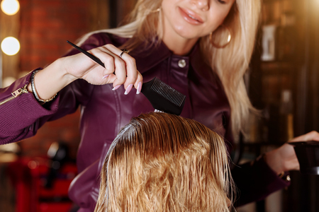 Close up shot of hands of hairdresser with brush applying mask or conditioner to hair of her client in beauty hair salon. Spa, care, hair health, problems with hair. Banco de Imagens