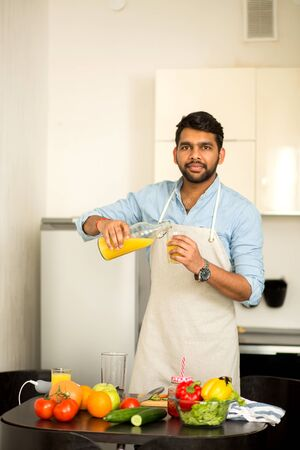Handsome unshaven indian man wearing blue shirt and apron pouring fresh organic orange juice into a glass looking at camera, prepearing breakfast in kitchen at home. Healthy vegan lifestyle.