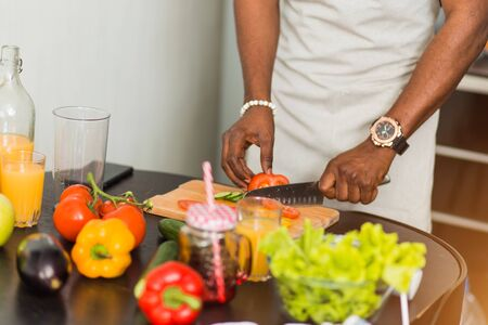Closeup cropped shot of african man preparing vegetable salad, holding knife, cutting tomatoes on chopping board in the kitchen at home. Vegetarian, healthy food concept.