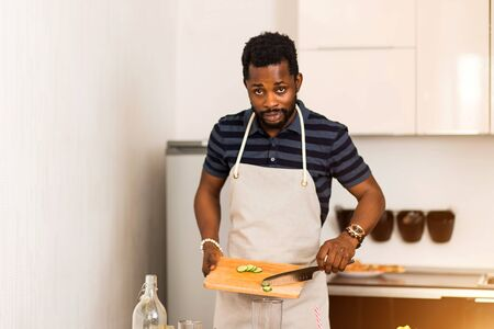 Portrait of handsome young unshaven black man cutting cucumber in the kitchen, cooking, preparing vegetable salad, looking inquiringly at camera.