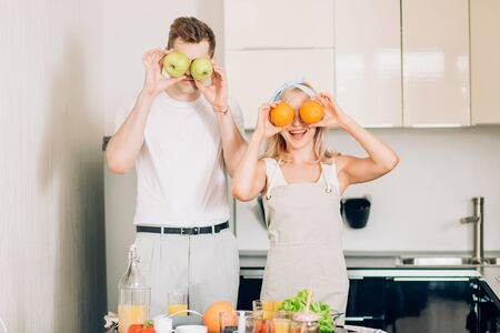 Romantic newly married couple cooking healthy food and having fun together in their kitchen at home. Caucasian woman and man preparing vegetable salad and fruit smoothie.