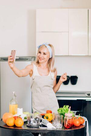 Imagen de adorable mujer caucásica con delantal tomando selfie en smartphone mientras cocina ensalada de verduras frescas en el interior de la cocina en casa. Estilo de vida saludable. Cocinar en casa.