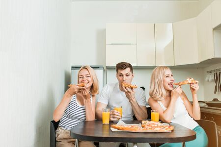 Friendship, people and food concept. Three caucasian happy students eating pizza in kitchen.They are having party at home, laughing and having fun, drinking orange juice.