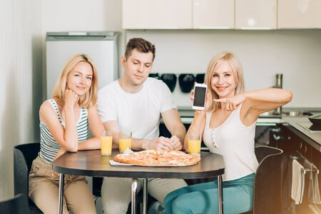 Attractive blonde caucasian girl enjoying pizza with friends in kitchen, holding mobile phone with empty screen and pointing it with finger, looking at camera with happy smile. Pizza delivery concept.