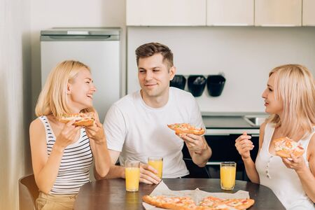 Young friends having party at home, eating pizza, drinking fruit juice and smiling. The cheerful company of youth people resting in kitchen. Friendship, people and food concept.