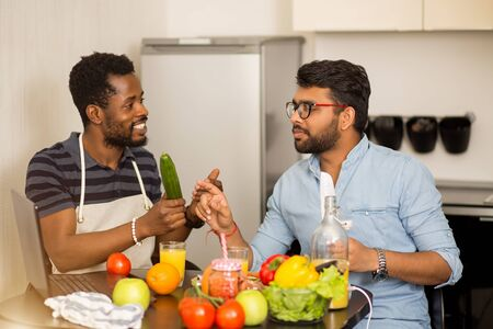 Two students argue what to cook for dinner. Multicultural friends sitting in kitchen, using laptop computer talking and preparing vegetable salad, smoothie together. People, food and cooking concept. Stockfoto
