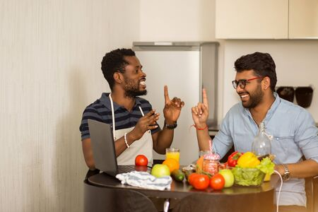 Multicultural friends sitting in kitchen looking each at other with raising index fingers in eureka gesture and laughing. Cheerful students cooking, having fun at home. People, communication concept.