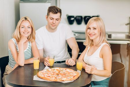 Two happy beautiful blonde Caucasian young women with their friend eating tasty pizza and drinking fruit smoothies, sitting at table in kitchen, smiling looking at camera.