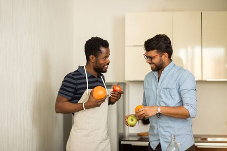 Two male students in casual clothes going to cooking smoothie standing in kitchen of hostel, holding grapefruit, orange, apple, tomato in hands, cheerfully talking and laughing.