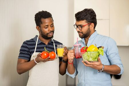 Closeup shot of two multi ethnic friends standing in light kitchen and holding fresh organic vegetables and glasses with fruit drinks. Healthy food, vegetarianism, cooking concept.