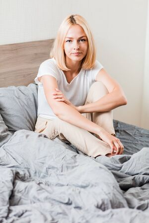 Serious thoughtful girl with blonde hair sitting on gray sheet looking at camera. Attractive caucasian female in domestic clothes resting at home in morning. Stockfoto