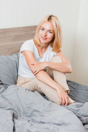 Beautiful caucasian blonde woman wearing sleepwear smiling looking at camera sitting on bed with gray bedding at home in morning. People, lifestyle, leisure and relaxation concept.