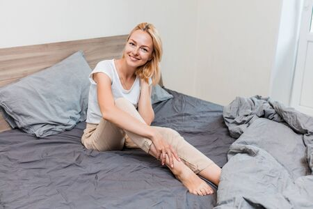 Portrait of happy laughing female awaking in good mood after healthy dream, sitting on comfortable bed in bedroom. Optimistic beautiful woman in sleepwear smiling posing in hotel room. Stockfoto