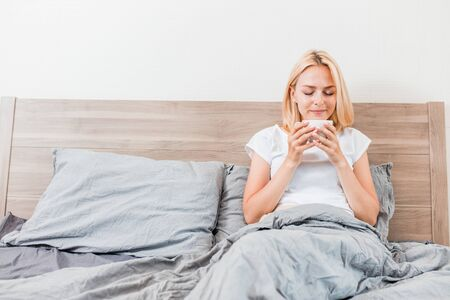 Gorgeous blonde lady drinking hot coffee in cozy bedroom. Indoor portrait of beautiful girl relaxing on bed in morning. Lifestyle, leisure, breakfast in bed, bedding concept. Stockfoto