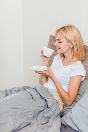 Side view of caucasian young blonde woman in white t-shirt sitting in her bed with cup of coffee after waking up. Vertical shot. Attractive female model resting at home in morning.