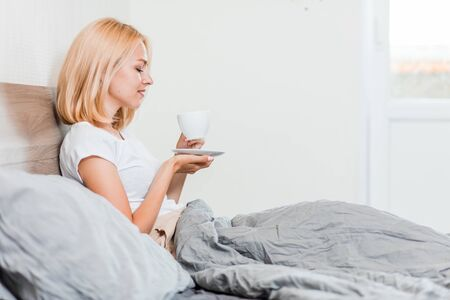 Profile portrait of gorgeous blonde lady drinking tea in light cozy bedroom. Indoor shot of beautiful caucasian girl relaxing on bed in morning. Lifestyle, leisure, breakfast, bedding concept. Stockfoto