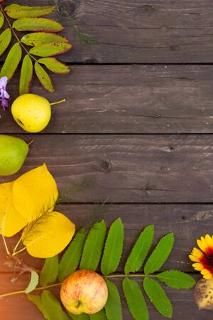 Vertical brown wooden background with autumn leaves, flowers and fruit with copy space for text