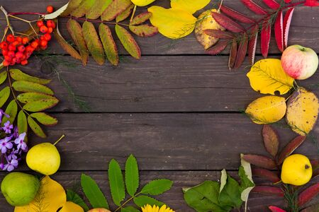 Beautiful frame of colorful autumn leaves, fruits and flowers on brown wooden background, top view. copy space