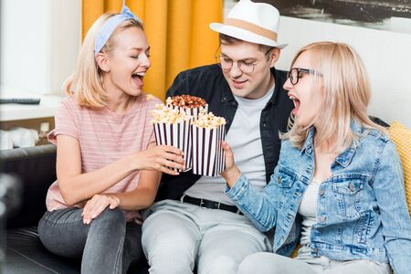 Three overjoyed friends spending day-off at home sitting on sofa watching sport match eating popcorn and celebrating win. Leisure, sport, happiness, entertainment concept. Home party.