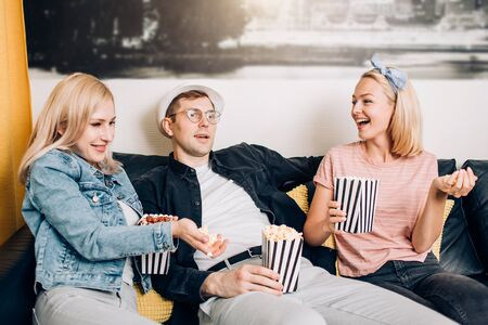 Happy friends relaxing sitting on couch and watching championship or funny TV show, enjoying popcorn together. Cheerful group of students having fun at home. Sport, people, leisure, friendship