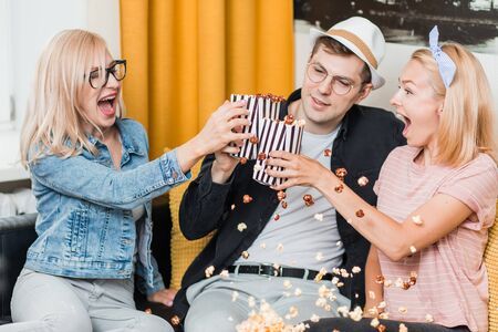 Two joyful young caucasian blonde women and man having fun, eating popcorn and enjoying together. Cheerful group of friends sitting on couch watching TV show and celebrating at home.