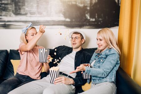 Indoor shot of group of happy friends wearing casual clothes having fun at home, sitting on sofa throwing popcorn and laughing. People, leisure, friendship and happiness concept.