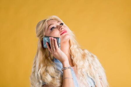 Portrait of caucasian blonde woman in casual outfit with long wavy hair talking on mobile phone, laughing, hearing terrific news, being happy on yellow background. Technology, communication concept. Фото со стока