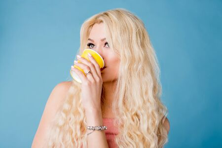 Beautiful young caucasian woman with long blonde hair, holding takeaway yellow paper cup, looking down with dreamy expression, enjoying cool beverage in hot summer day isolated sky blue background.