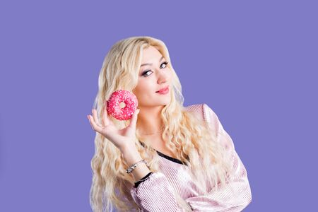 Charming young lovely long haired blonde female holding sweet doughnut, proposing you to eat delicious dessert, smiling posing against purple background. Gorgeous caucasian girl with donut.