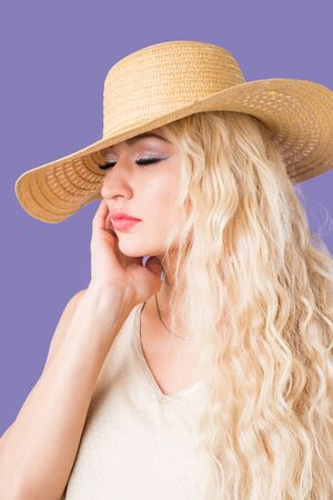 Photo of attractive woman with long blonde hair, green eyes, perfect skin, plump lips, makeup wearing summer dress, raising her beige straw hat wanting to tan. Summertime, vacation, sunscreen concept.