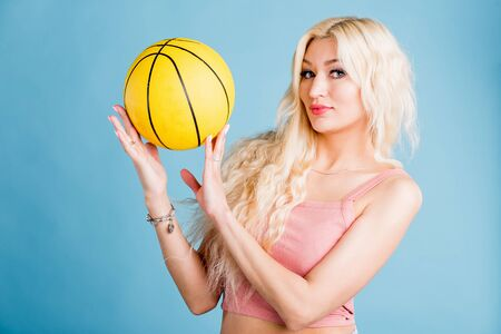 Young attractive woman with blonde long hair, nice makeup, manicure wearing pink short top holding basketball looking at camera with pleasant expression against light blue background.