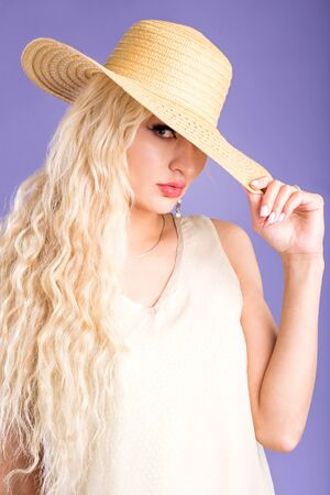 Fashion photo of attractive woman with long blonde hair, green eyes, perfect skin, plump lips looking at camera with open mouth, wearing straw hat, summer dress. Close up, copy space