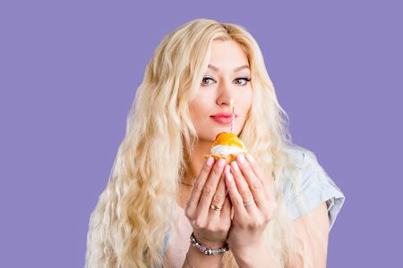 Happy cute lovely curly young blonde woman with makeup wearing casual clothes holding birthday cupcake with candle smiling isolated on violet background. Birthday, holiday concept. Фото со стока