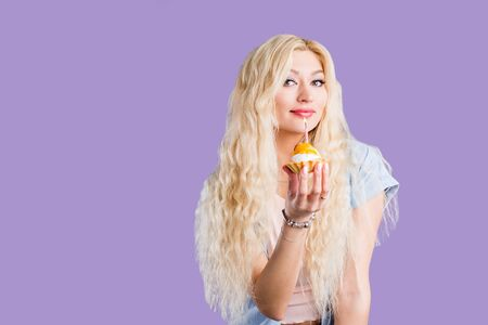 Portrait of a seductive sexy young woman with long curly blonde hair, bright makeup holding cake with candle and tasting it over violet background. Birthday, holiday concept.