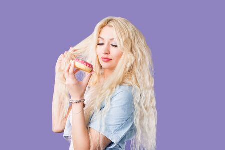 Hungry caucasian blonde woman holding tasty pink glazed doughnut, going to eat it, having unhealthy nutrition, breaking the diet, can not imagine life without sweet desserts, on purple background. Фото со стока