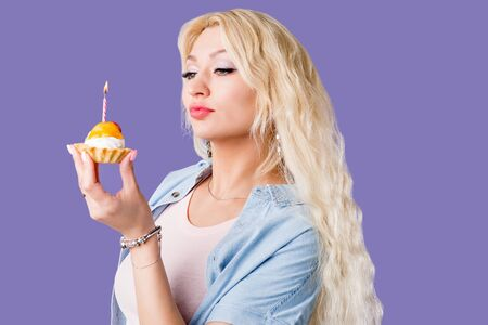 Beautiful woman with long wavy blonde hair holding small cake with cream, pieces of fruits and candle smiling looking at camera. Birthday, holiday. Studio portrait over lilac background. Фото со стока - 129812280